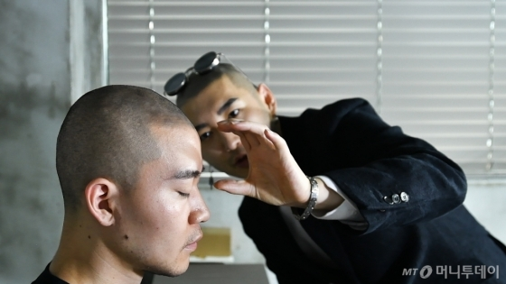 '대머리 디자이너' 디 크리스가 고객에게 맞춤형 디자인을 해주고 있다. /사진=이상봉 기자