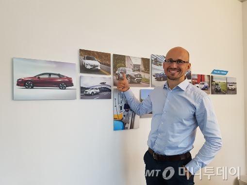 'H2 모빌리티'의 니콜라스 이반 CEO가 사무실에 붙여놓은 현대차의 차세대 수소전기차 '넥쏘' 사진 앞에서 포즈를 취하고 있다./사진=최석환