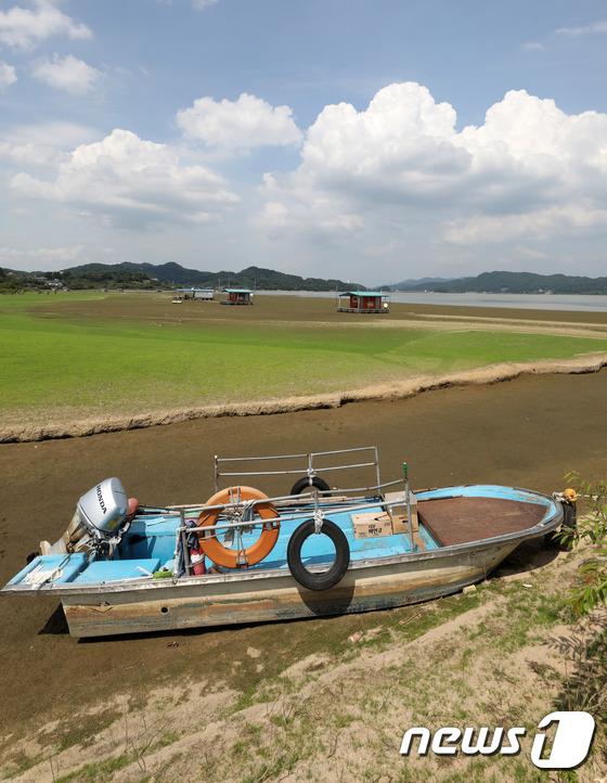 [사진]최강 폭염 '바닥 드러난 저수지에 발 묶인 낚시배'