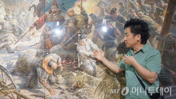 ACC 복합6관에서 전시중인 '북한 미술: 사회주의 사실주의의 패러독스'전에서 문범강 교수가 북한의 홍명철·서광철·김혁철·김일경 작가의 집체화 '평양성 싸움'에 대해 설명하고 있다.