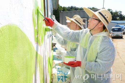 오병관 농협손보 대표이사가 헤아림 봉사단원들과 벽화를 그리고 있다./사진=농협손보