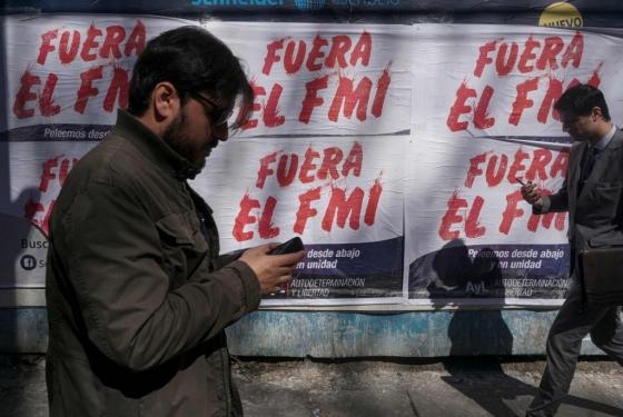지난 4일(현지시간) 아르헨티나 부에노스아이레스에서 시민들이 IMF(국제통화기금) 지원을 반대하는 포스터 앞을 지나고 있다. /AFPBBNews=뉴스1