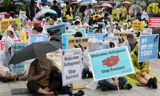 16일 서울 보신각에서 열린 난민 환영 집회에 참석자들이 '난민을 지원하자'라는 손피켓을 들고 있다. / 사진=뉴스1