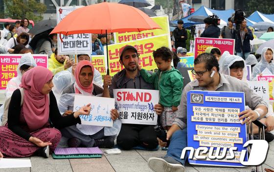 [사진]우산 쓴 난민 가족
