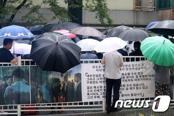 [사진]가산동 싱크홀 사고...주민들 우산쓰고 공청회