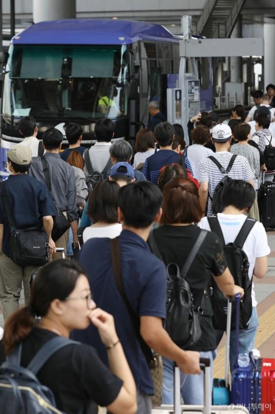 6일 태풍 '제비'가 강타한 일본 간사이공항에 발이 묶였던 여행객이 이즈미사노 시로 이동하기 위해 특별 수송 버스를 타고 있다. © AFP=뉴스1