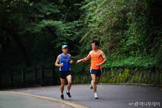 안기형 현대모비스 모듈품질보증팀 차장이 'VMK 한국시각장애인 마라톤 대회'에서 한 시각장애인의 동반주자로 달리고 있다./사진=현대모비스