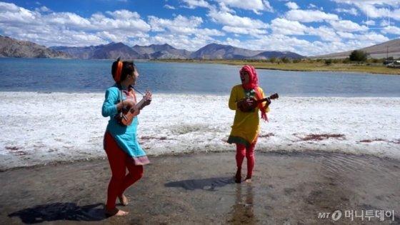 호숫가에서 우쿨렐레를 연주하고 있는 위경은(왼쪽), 김연우씨./사진=김연우, 위경은씨 제공
