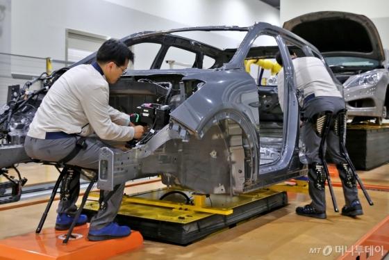 현대자동차 직원이 '의자형 착용로봇(H-CEX)'을 착용하고 작업하고 있다./사진제공=현대차