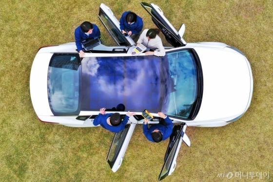 현대·기아차 환경에너지연구팀 연구원들이 지난 30일 경기도 의왕연구소에서 2019년 양산을 목표로 하고 있는 '1세대 솔라루프'가 장착된 차량을 시험하고 있다. 하이브리드 모델에 적용할 1세대 솔라루프는 일반 루프(지붕)에 양산형 실리콘 태양전지를 장착한 형태다. 1시간 태양광을 받으면 100Wh(와트아워) 에너지를 저장하는 것이 가능하다는 게 현대·기아차측 설명이다./사진제공=현대∙기아차
