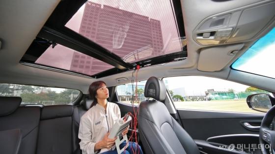 현대∙기아차 연구원이 투광이 가능한 2세대 솔라루프가 설치된 자동차 안에서 효율을 측정하고 있다./사진제공=현대∙기아차