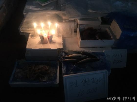 이달 7일 오전 전기와 물이 끊긴 노량진 구 수산시장에 한 상인이 촛불을 켠 채 영업을 이어가고 있다. /사진=서민선 인턴기자
