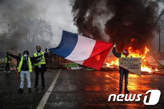 프랑스 노란조끼 시위 중 프랑스 국기를 든 시위 참가자들 © AFP=뉴스1