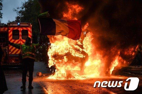지난 1일(현지시간) 프랑스 파리에서 열린 '노란조끼' 시위에서 한 남성이 불타는 차량 앞에서 프랑스 국기를 든 채 에마뉘엘 마크롱 정부의 친기업 정책에 항의하고 있다.  © AFP=뉴스1