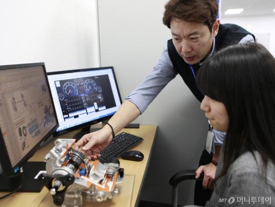 현대위아 연구원들이 12일 경기도 의왕시 현대위아 의왕연구소에서 4륜 구동 통합 제어 부품인 '전자식 커플링'을 테스트하고 있다. /사진제공=현대위아<br />