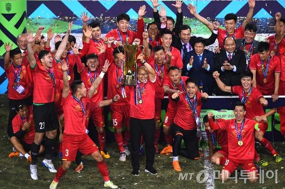 박항서 감독(가운데)이 지난 15일(한국시간) 베트남 하노이의 미딩 국립경기장에서 2018 아세안축구연맹(AFF) 스즈키컵 우승 트로피를 들어 올리고 있다. /AFP=뉴스1