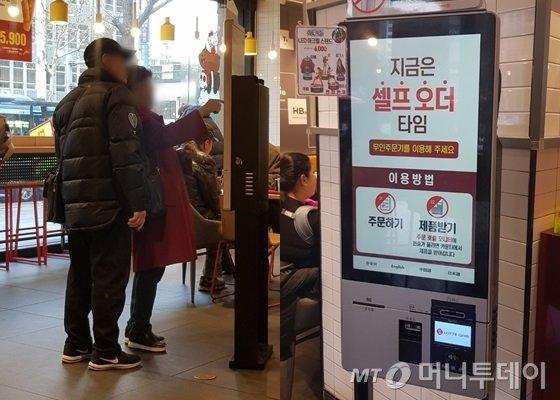지난 19일 서울 종로구의 한 패스트푸드 전문점. 60대 고객이 '셀프 오더 타임'에 무인 주문기로 주문을 넣다 주변인에게 도움을 청하고 있다. /사진=박가영 기자