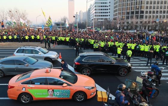 주요 택시단체 조합원들이 지난달 20일 서울 여의도 국회의사당 앞에서 카풀 반대 집회를 개최한 뒤 마포대교 방향으로 행진하고 있다. 행렬 옆 도로로 한 택시가 지나치고 있다.<br />