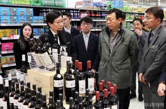 신동빈 롯데회장이 12일 인천터미널점 롯데마트의 와인코너에서 설명을 듣고있다./사진=롯데