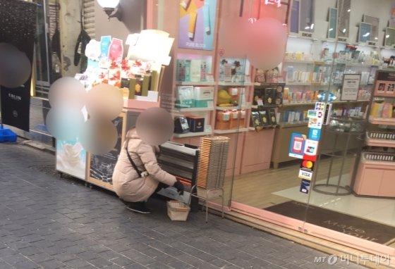 서울 중구 명동 소재 한 화장품 매장 앞에서 판촉 요원이 쭈그리고 앉아 정리를 하고 있다./사진=남형도 기자