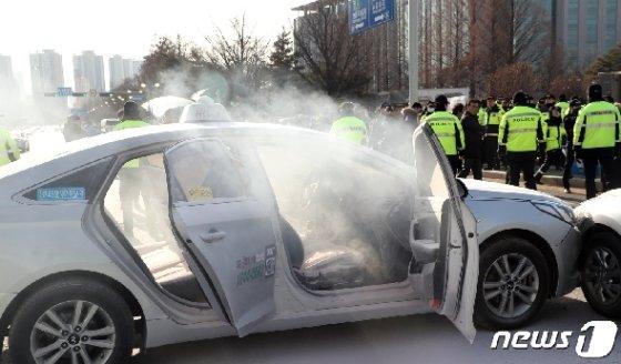 11일 오후 서울 여의도 국회 정문앞에서 한 택시기사가 분신을 시도해 경찰들이 화재진압을 하고 있다. 2019.2.11/뉴스1 © News1 김명섭 기자