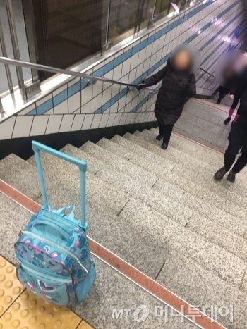 """가방을 계단 위로 옮겨드리자 할머니는 연신 """"고맙다""""며 미소 지었다./사진=남형도 기자"""