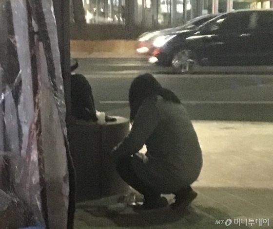 바닥에 떨어진 전단지를 줍기 위해 무릎을 굽힌 아주머니. 한 장의 무게는 결코 가볍지 않았다./사진=남형도 기자