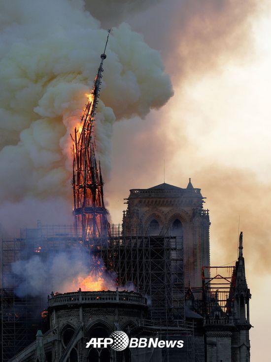 15일 오후 6시50분(현지시간)쯤 파리 구도심 내 시테섬에 있는 노트르담 대성당 화재로 불에 탄 첨탑이 무너지고 있다./사진= AFPBBNews=뉴스1