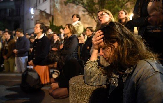 """15일 (현지 시간) 프랑스 파리 구도심 시테섬 동쪽에 위치한 노트르담 대성당의 화재 현장에서 시민들이 무릎을 꿇고 지켜보고 있다. 에마뉘엘 마크롱 대통령은 이날 현장을 방문해 눈물을 보이면서 """"끔찍한 비극""""이라 말하고 """"노트르담 대성당을 다시 세울 것""""이라고 말했다.© AFP=뉴스1"""