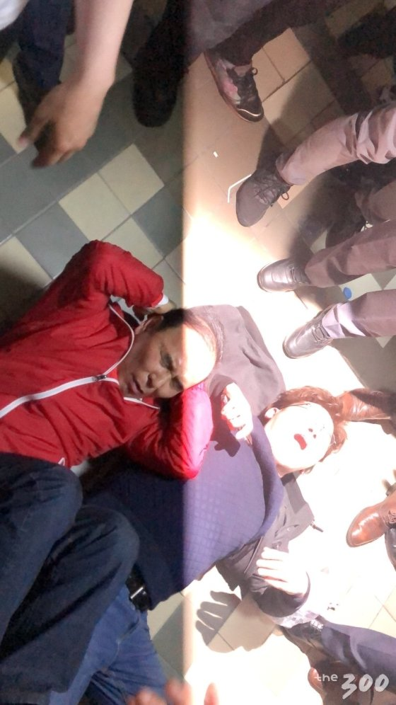 박덕흠 자유한국당 의원(붉은색 옷)이 26일 새벽 2시15분쯤 점거농성 중 뒤로 누웠다/사진=이재원 기자
