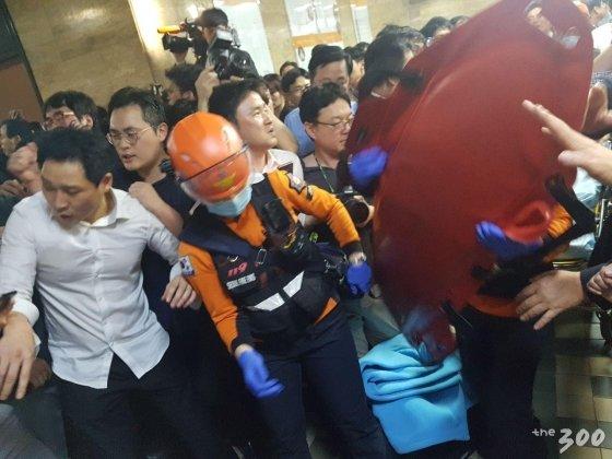 박덕흠 자유한국당 의원이 26일 새벽 2시15분쯤 점거농성 중 뒤로 쓰러졌다. 이후 출동한 119구급대가 박 의원을 들것에 실어 옮기고 있다./사진=이재원 기자