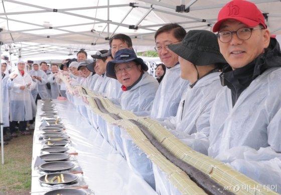 LG디스플레이가 지난 25일 경기도 파주 사업장에서 진행한 '2019 목표달성 결의대회'에서 한상범 부회장(우측 네번째)과 임직원들이 함께 대형 김밥을 만들고 있다./사진제공=LG디스플레이