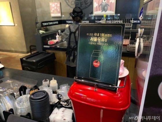 """20일 서울 무교동 탐앤탐스에 """"이곳은 국내 1위 브랜드 서울우유를 사용하는 카페입니다.""""라고 적혀 있는 홍보 문구가 커피 머신위에 세워져 있다. /사진=이강준 기자"""