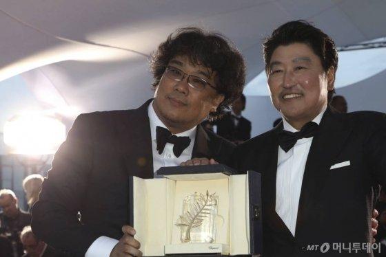 【칸=AP/뉴시스】봉준호(왼쪽) 감독이 25일(현지시간) 프랑스 칸에서 열린 제72회 칸 국제영화제시상식에서 영화 '기생충'으로 '황금종려상'을 받고 배우 송강호와 함께 포즈를 취하고 있다.