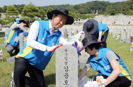 진옥동 신한은행장(앞줄 왼쪽)과 임직원들이 12일 서울시 동작구 국립서울현충원에서 순국선열들의 묘역을 정비하고 있다. / 사진제공=신한은행