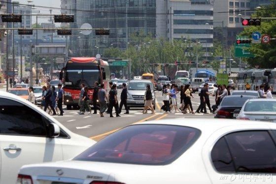 13일 오후 서울 중구 정부종합청사 주변을 지나는 시민들과 차량들. /사진=임성균 기자