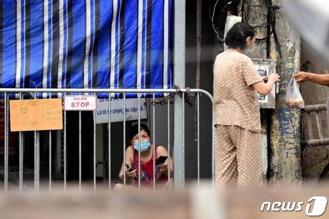 8월 24일 (현지시간) 코로나19 확산으로 봉쇄 조치가 내려진 베트남 하노이에서 주민이 바리케이드 뒤에서 음식을 기다리고 있다. /사진= AFP=뉴스1