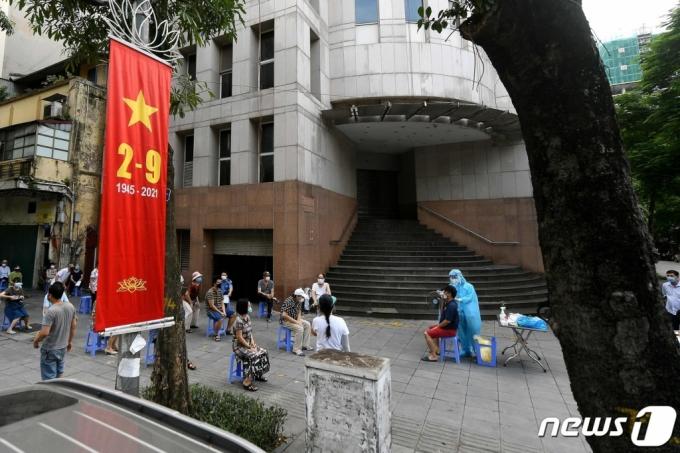 (베트남 하노이 거리에서 주민들이 코로나19 면봉 검사를 받고 있다.   /사진=AFP=뉴스1