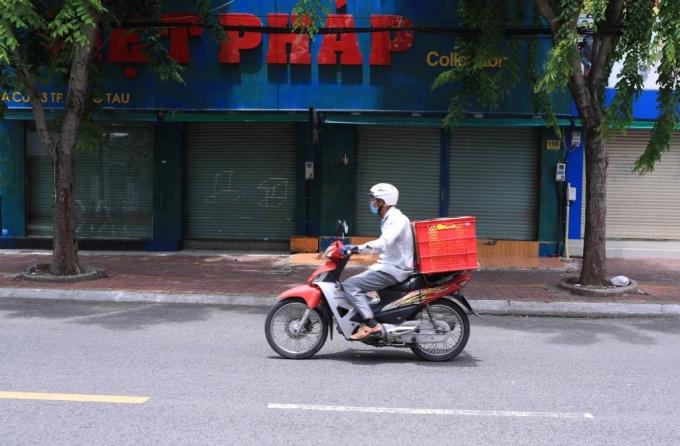 [붕따우=AP/뉴시스] 19일 베트남 붕따우에서 한 배달원이 스쿠터를 타고 코로나19 봉쇄로 문 닫은 상점가를 지나고 있다. 4천만 명에 가까운 인구를 가진 남부 베트남은 코로나19의 기록적인 증가로 2주간 봉쇄에 들어갔다. 2021.07.19.