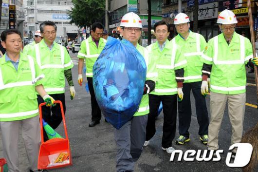[사진]쓰레기 봉투 옮기는 김황식 총리
