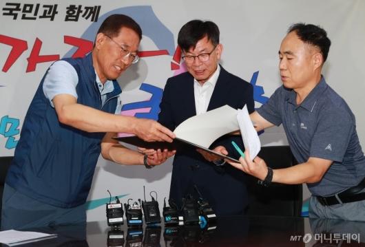 [사진]대선당시 정책연대 협약서 살펴보는 김상조 정책실장