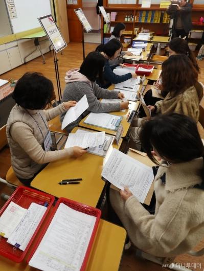 [사진]입학 신청서 작성하는 학부모들