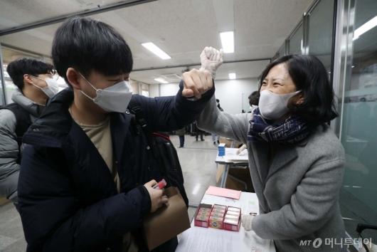 [사진]팔꿈치 인사로 수능 응원