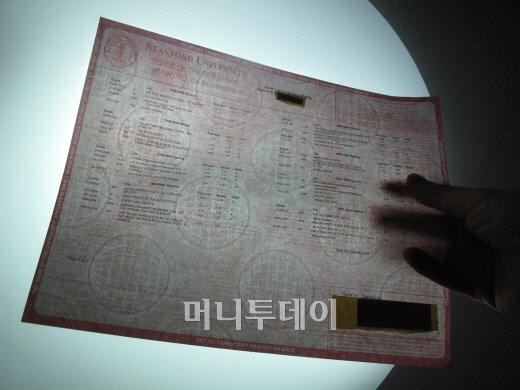 ↑불빛에 비춰 나타난 진본 확인용 지구본 모양 아이콘<br />