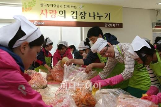 ▲13일 송파구 소재 보인 고등학교에서 100여명의 한국투자증권 직원들이 독거노인을 위한 김장김치 4000kg을 담고 있는 모습.<br />