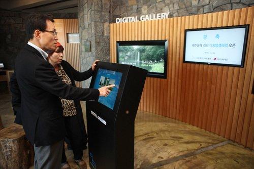 ↑제주 올레 사무소내의 쉽터를 리모델링해 조성한 'LG 제주올레 디지털 갤러리'에서 남상건 LG상록재단 부사장과 서명숙 사단법인 제주올레 이사장이 직접 디지털 갤러리를 시현하고 있다.