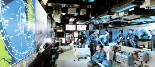 한·미 연합훈련 이틀째인 29일 조지 워싱턴 항공모함 작전통제실에서 지휘관들이 작전을 통제하고 있다. 상황실 레이더 화면에 북한 전역은 물론 인근 지역까지 포함하는 조지 워싱턴함의 작전지역이 표시되고 있다. [사진공동취재단]<br />