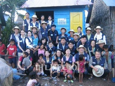 ↑국민은행 사회봉사단원 30여 명은 지난해 10월  캄보디아를 찾아 주택 2채를 신축하고 병원도색 등의 봉사활동을 펼쳤다. (사진: 국민은행 제공)<br />