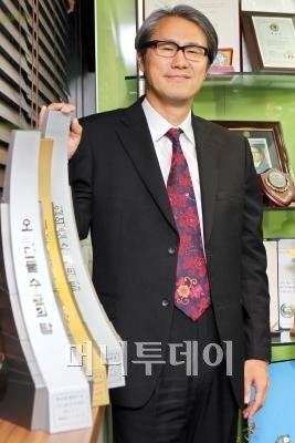 ↑ 김태섭 케이디씨그룹 회장이 '1억달러 수출탑'을 자랑스럽게 들어보이고 있다. ⓒ홍봉진 기자 honggga@