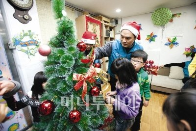GS칼텍스 임직원들이 연말 릴레이 봉사활동의 일환으로 소외된 이웃을 찾아 아이들과 함께 크리스마스 트리를 만들고 있다.